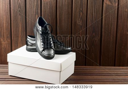 Leather Upper Metallic Trandy Womens Shoes On Brown Wooden Background. Shopping Purchases