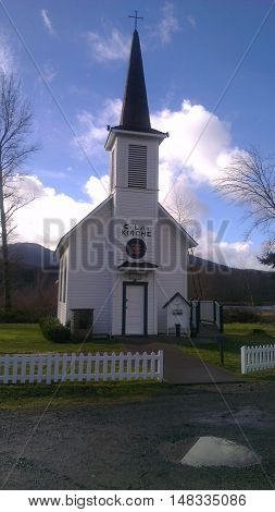 Little old fashioned white chapel outside of mount Rainier in Washington.