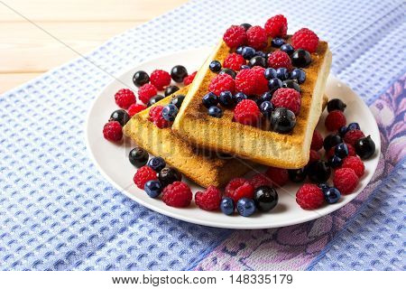 Fresh brussels waffle with blueberry raspberry and blackcurrant. Breakfast soft waffles with fresh berries