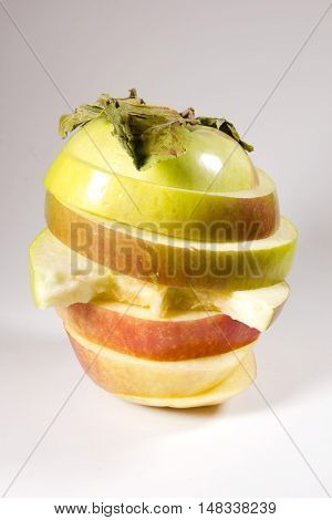 Ripe apple sliced in layers on a gray background