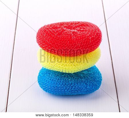round sponges for washing dishes in different colors located on top of the white wooden table
