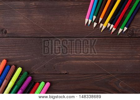Colored pencils on a wooden board. School supply with copy space for text