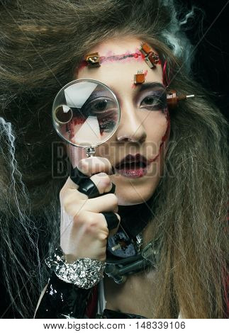 Young woman with creative make up holding a magnifying glass