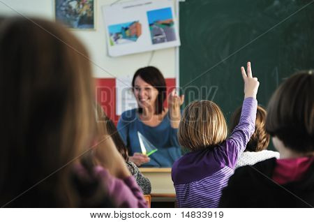 happy young teacher woman at elementary school teaching and giving leassons to group of young smart children