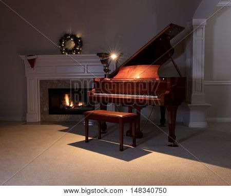Piano with reading light on with glowing fireplace and Christmas decorations in background. Select focus on front of piano.