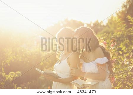 Two sisters read books in the backyard. Girl showing her sister something interesting in his book. Shoot in the rays of the setting sun. Soft focus and creative effects.