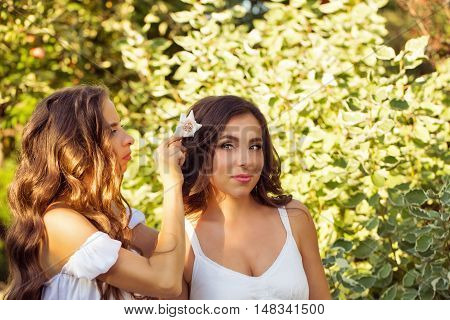 Two sisters. Girl weaves flowers in hair sister. Family time. Human relationships.