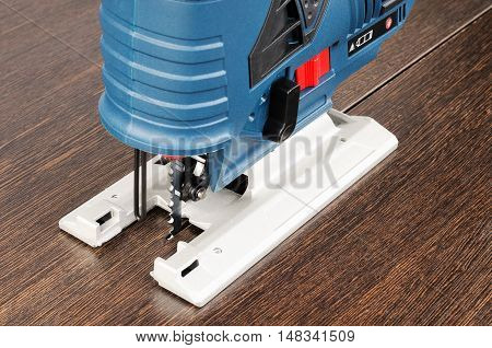Blue electrical fretsaw on brown wooden surface