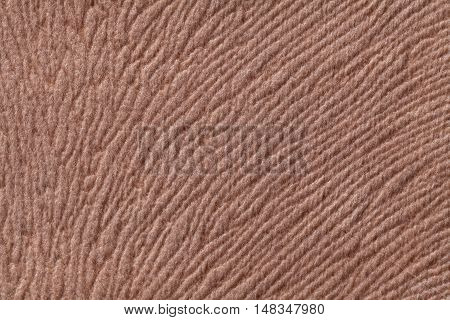 Light brown background from a soft wool textile material closeup. Fabric with natural texture. Cloth backdrop.