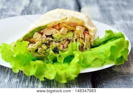 Fresh roll of pita bread, chicken and vegetables with natural yogurt and lettuce on a white plate on wooden boards. Healthy food. Diet