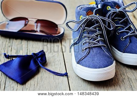 Children's fashion. Denim sneakers, glasses case and a blue pouch for accessories on wooden background