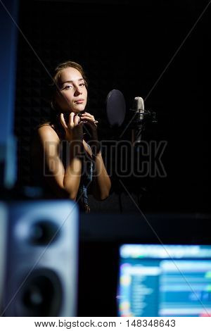 Young girl with headphones in professional condenser studio, studio computer equipment in frame