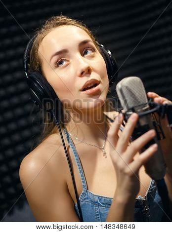 young girl singing into a microphone in a studio