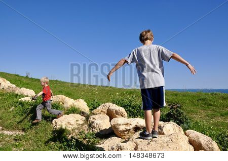 HAMILTON HILL,WA,AUSTRALIA-AUGUST 8,2014: Kids hiking and playing on the limestone rocks on the trails in Manning Park with Indian Ocean view in Hamilton Hill, Western Australia.
