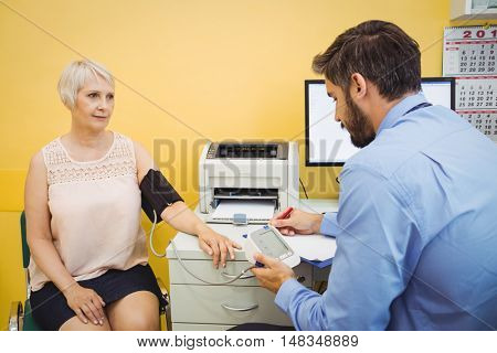 Doctor checking blood pressure of patient at the hospital