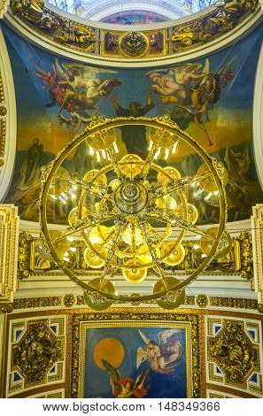 SAINT PETERSBURG RUSSIA - APRIL 25 2015: The chandelier and painted ceiling of St Isaac's Cathedral depicting the scenes from Holy Bible on April 25 in Saint Petersburg.
