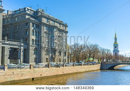 The grey building of Lendoc Art Center with the tall bell tower of the Sailors' Cathedral on the background St Petersburg Russia.