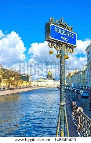 The signboard of Potseluev Bridge (Bridge of Kisses) across the Moyka river with the golden dome of the St Isaac's Cathedral on the background Saint Petersburg Russia.
