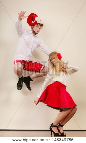 Happy cute couple dancing and jumping in studio. Pretty woman and handsome man in santa claus hat having fun. Christmas xmas season.