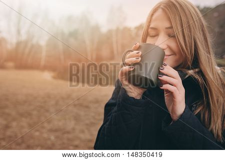dreamy young woman drinking hot tea outdoor on the walk enjoying traveling in autumn weekend