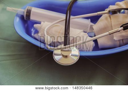 Stethoscope bandages syringe in blue container medical equipments toning