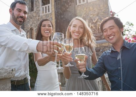 Happy adult people clinking champagne glasses at party