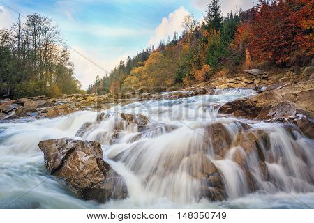 Landscape mountain river in autumn forest. View of the stony rapids. Fast jet of water at slow shutter speeds give a beautiful magic effect