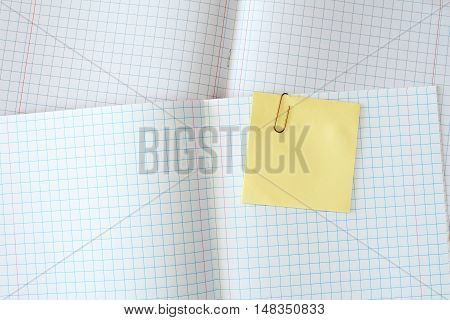 Squared exercise book with blank yellow sticky note