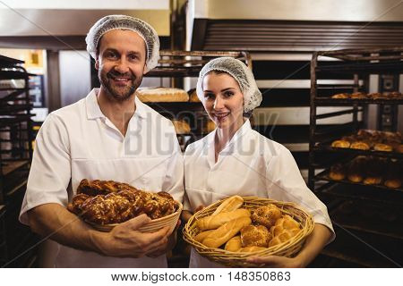 Portrait of female and male baker holding basket of bread and sweet food in bakery shop