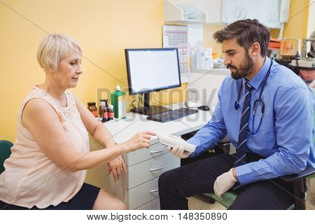 Doctor measuring sugar level of patient with glucometer at the hospital