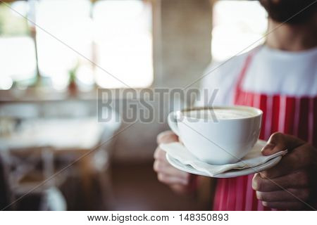 Mid-section male baker holding a cup of coffee in bakery shop