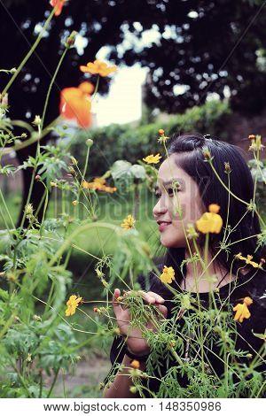asian young girl hiding among flowers in garden