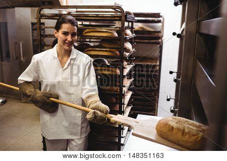 Female baker baking fresh bread in bakery shop