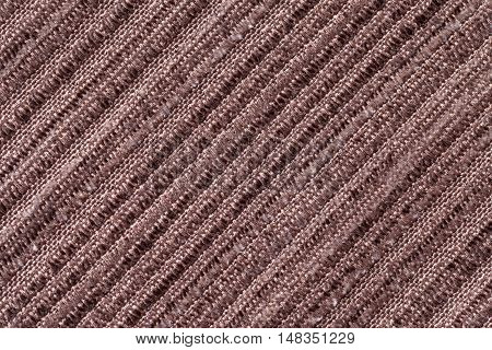 Brown background of a knitted textile material with diagonal pattern. Fabric with a striped texture closeup.