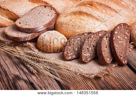 Fresh bread, ears of ripe wheat, baked goods, harvest on the farm, lots of baked goods, a table of old wood, close-up bread, wood grain