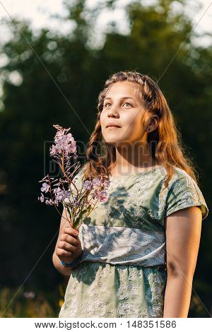 Portrait of a beautiful young teenage girl with a branch of willow in his hands