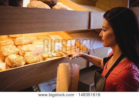 Female baker packing sweet food in bakery shop