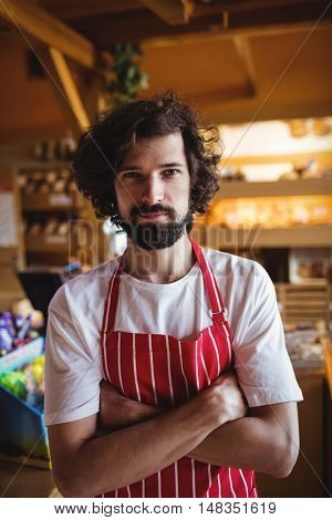Portrait of male baker standing with arms crossed in bakery shop