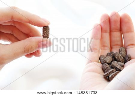 Pills in a female hand on a white background. A handful of dark tablets