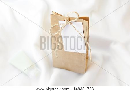 Kraft bag with a label for an inscription on a white blanket