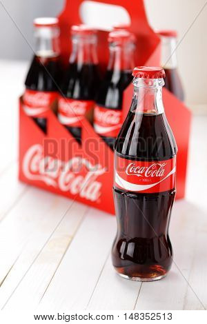 Brest Belarus - September 21 2016: Coca-Cola Classic drink in a glass bottle with cardboard box pack on background