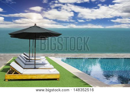 Blurred Blue Sea And White Sand Beach With Parasol, Beach Chair And Some People - Holiday And Vocati
