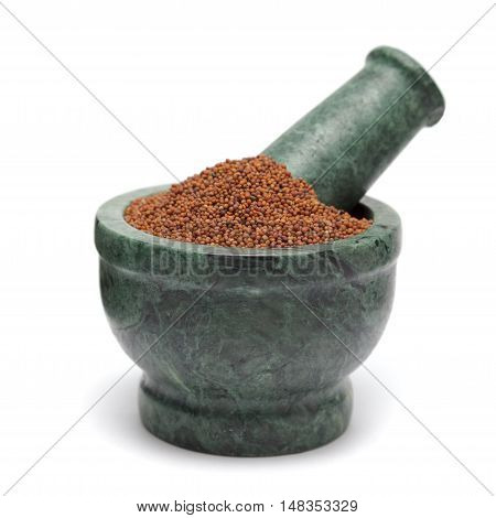 Organic Small Brown Mustard Seeds (Brassica juncea) on marble pestle. Isolated on white background.