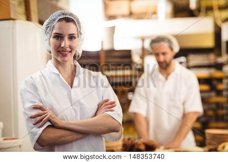 Portrait of female baker standing with arms crossed in bakery shop