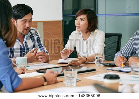 Vietnamese business lady sharing her idea with colleagues