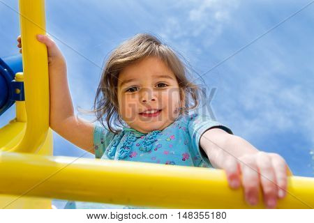 A little girl up on a jungle gym with a blue sky in the background. She is looking down at the camera. Her face is messy.