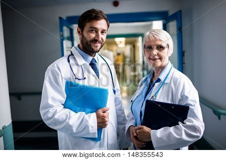 Doctors standing together with clipboard and file in hospital