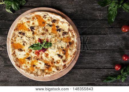 Delicious fresh Pizza with walnuts, cheese and tomato paste on the wooden background. Top view.
