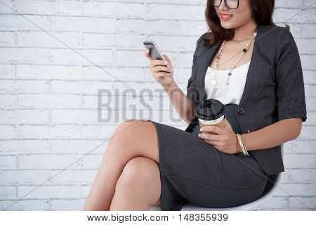 Business lady sitting on chair and reading messages in her phone