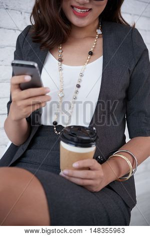 Cropped image of smiling business woman enjoying coffee when checking smartphone